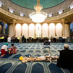 London, UK - 21 July 2012: Two children and a man sit during the prayer for the breaking of the fast of Ramadan during the Iftar 2012 celebrations at the London Central Mosque in Regent's Park