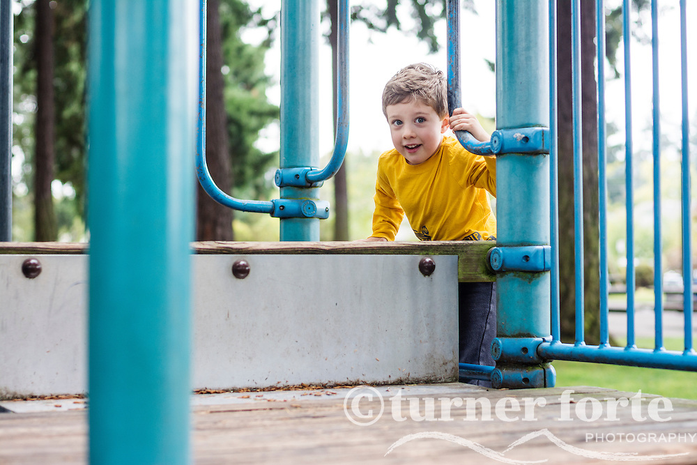 Toddler boy successfully climbs to top of play structure at playground in Portland, Oregon.