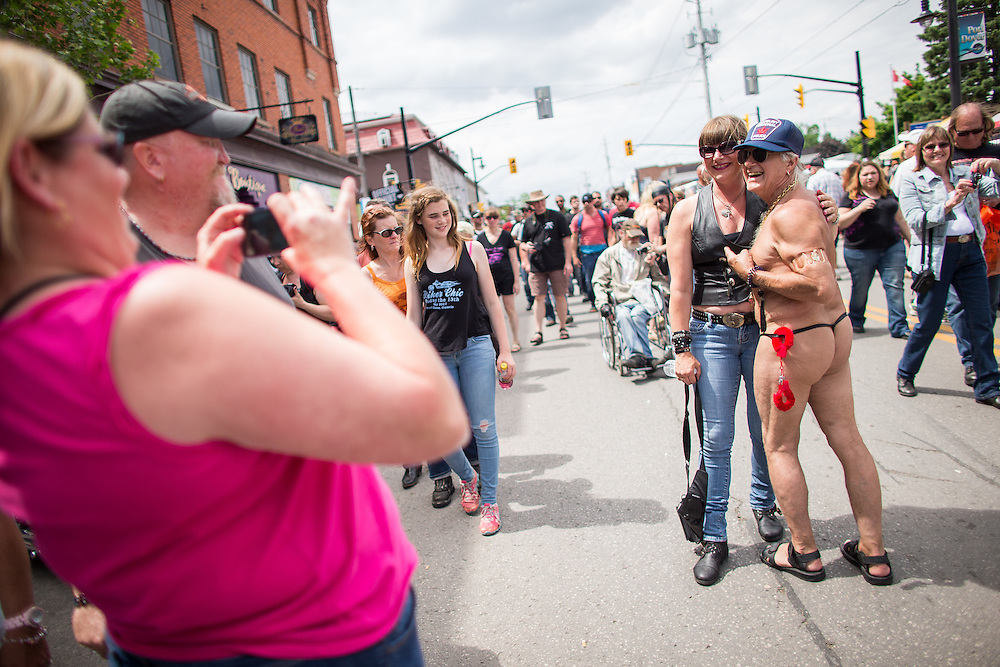 Sylvia Lackie of Sarnia poses for a photo with &quot;thong man&quot; Paul Nurmi, of Hamilton, during Friday the 13th celebrations in Port Dover Ontario, Friday,  June 13, 2014.<br /> THE CANADIAN PRESS/ Geoff Robins