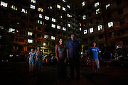 Daai Chin refugees from Burma, (L-R) Rose Pam, 10, Sho Hlai Ling, 12, Theing Mana, Pastor Bu Naing Ling, 58, and Shang Phu Lang Thang, 15, from Chin State, pictured outside their apartment block in Kuala Lumpur, Malaysia. <br /> <br /> &quot;Mindat is the capital town in the southern part of Chin State, from Mindat to my village, Makuiimnu,  takes 3 days and 2 nights walking.<br /> <br /> The southern part of Chin State is where Buddhism is spreading and many people are being lured to become Buddhists by the government. If they convert they are promised many things. I became a Christian in 1981 and started preaching the word of God. I traveled to all the villages and preached the gospel to the Chin people and I learned all about these things. I was banned from spreading the word of God and the church that I was building was stopped and I was threatened in many ways. They [ the government] stopped giving me the travel documents to travel around the villages. <br /> <br /> I had to report every night to the authorities, whenever I reported to the head of the locals I had to pay them. For me whenever I come across anyone I talk to them about the gospels, I don't care if they are Buddhists, I talk to everyone. Finally I was brought to the head of the town and forced to sign [a document] that I would stop preaching. I just signed this to please them but I kept on distributing leaflets and doing what I'm supposed to do, I'm not a politician and I don't do any politics.<br />  <br /> I was an evangelist and I did my best to spread the word of God. Buddhists and Catholics were giving villagers money to convert them, the competition was so intense that the Buddhist monk who was converting people planned to assassinate the Roman Catholic Father in Mindat; the man he paid a lot of money to assassinate the priest tried, but the gun misfired. <br /> <br /> Many of the preachers like me are forced to do labour and are interrogated many times and always have to report everywhere t