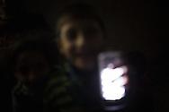Kids playing with a torch light in the Al Shale' refugee camp. Bambini giocano con una torcia nel campo rifugiati di Al Shale'.