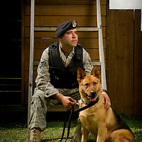 Staff Sgt. Jonathan Campbell and his working dog Rony, an eight-year-old German Shepard, sit on an obstacle at the agility course at the 628th Security Forces Squadron working dog kennel at Charleston Air Force Base, SC, on July 7, 2011.