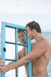 good looking man in the ocean with a mirror