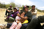 A 6-year-old girl cries in the arms of her aunt after they and the others in their group were apprehended by the U. S. Border Patrol about 28 miles north of the Arizona - Mexico border on the Tohono O'odham Nation.  The girl walked for two days in temperatures exceeding 110 degrees in hopes of joining her mother in New York.