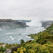 The town of Niagara Falls in Ontario, Canada, gives excellent views of all three sections of Niagara Falls, which drops 167 feet (51 m). Niagara Falls has the highest flow rate of any waterfall in the world. Niagara Falls is the name for the combined flow of Horseshoe Falls, American Falls and Bridal Veil Falls, on the Niagara River along the international border between Ontario, Canada and New York, USA. The Niagara River drains Lake Erie into Lake Ontario. Horseshoe Falls is the most powerful waterfall in North America, as measured by vertical height combined with flow rate. The falls are 17 miles north-northwest of Buffalo, New York and 75 miles south-southeast of Toronto. The panorama was stitched from 4 overlapping photos.