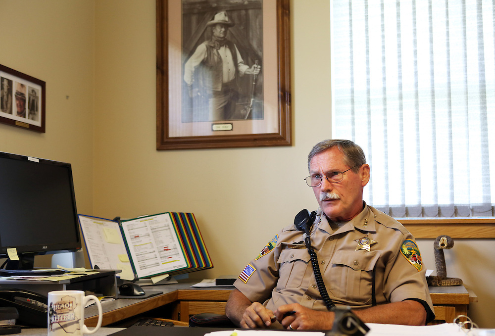 Sheriff Gil Gilbertson in his colorfully decorated office. Since federal timber payments have ceased in Josephine County and other parts of Southwest Oregon, the tax-base has shrunk. In Grants Pass, the county seat, shoplifting and other property crime are up, and law enforcement personnel numbers are down.