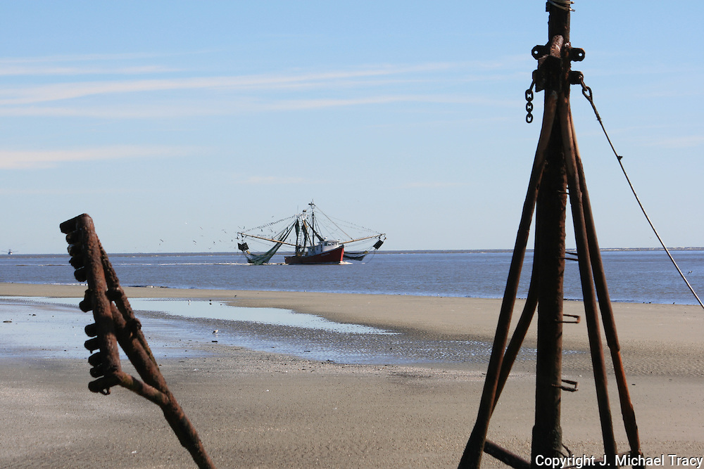 Shrimp Boat heading for port along Jekyll Island Beach framed by an ancient shrimp boat wreck buried in the beach sand.