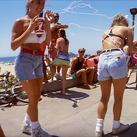 Madhattan Beach on the 4th of July, 1988 - If you add a little holiday spirit and alcohol to the Strand in Manhattan Beach, you get something called Madhattan Beach where you might see anything, like girls wearing matching patriotic cut-offs, being attacked by a guy with silly-string. From Widelux Beach available at Kim Reilly Arts on Manhattan Ave. in Manhattan Beach, California. (310) 372-3681