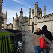 Oxford University student lovers walk through cobbled Radcliffe Square with All Souls College right and Radcliffe Camera left.