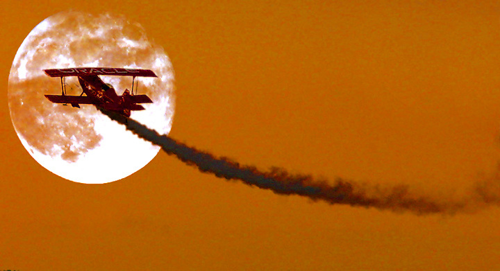 The Oracle bi-plane performs for the crowd during a Rose Festival Air Show twilight performance at Hillsboro Airport.