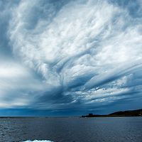 Canada, Manitoba, Churchill, Summer storm clouds above iceberg floating in Hudson Bay