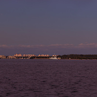 The full moon rises over Miami harbor, Virginia Key, the Rickenbacker Causeway and the Port of Miami with Fisher Island and Miami Beach buildings in the background.