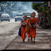 A trio of novice Buddhist monks walks in Mae Sot, Thailand on their morning rounds.