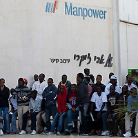 """Sudanese refugees wait outside the Immigration and Borders Authority to receive a visa in the city of Eilat on  February 27 2011. The municipality hung 1,500 red flags around the city as a sign of warning and put up hundreds of banners reading: """"Protecting our home, the residents of Eilat are drawing the line on infiltration."""" Eilat Mayor Meir Yitzhak Halevi said that 10 percent of the city's population was currently made up of migrants and that the residents feel that the city has been conquered...Photo by Olivier Fitoussi."""