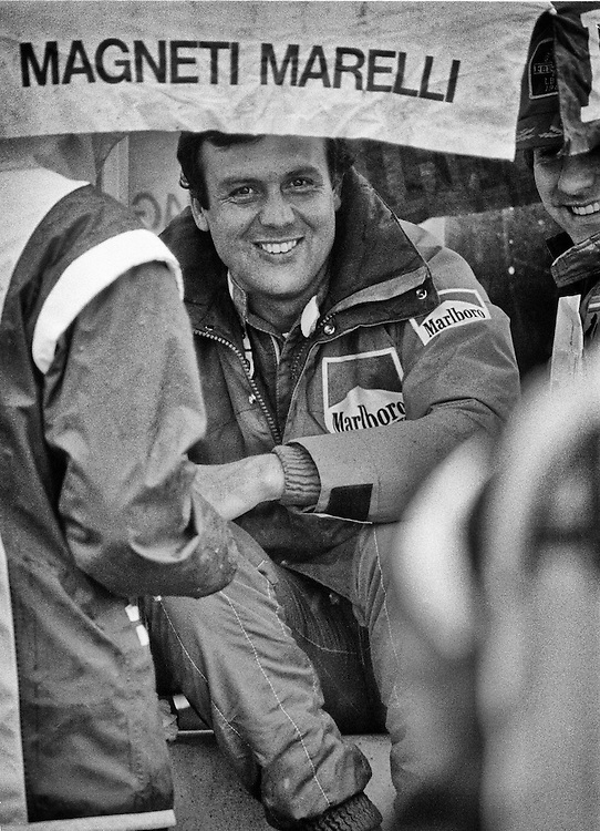 French F1 driver Patrick Tambay took over the Scuderia Ferrari race seat of his great friend, Gilles Villeneuve, following his tragic death in 1982 during the Belgian Grand Prix. <br /> <br /> He thrilled Ferrari fans world-wide when he brought Gilles&rsquo; #27 to victory that same year at the Germany Grand Prix at Hochenheim. It was also his first Grand Prix victory. <br /> <br /> Here in 1983, he enjoys a few quiet moments  before qualifying in unseasonably cold June conditions on the tight Detroit Grand Prix street circuit.