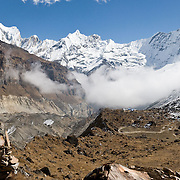 Machhapuchhre (or Machhapuchhare), the Fish Tail Mountain (on the right; 22,943 feet / 6997 meters elevation), is a sacred peak, illegal to climb, in the Annapurna Range of Nepal. This view is from Annapurna South Base Camp (ABC, at 13,550 feet elevation) in the Annapurna Sanctuary.  The left peak is Annapurna III (24,786 feet / 7555 meters). The sharp center peak is Gandharba Chuli (20,500 feet / 6248 meters). (Panorama stitched from 2 images.)
