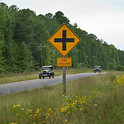 "Vintage autos pass by a ""Tank Crossing"" sign on Route 40 at Fort Pickett. Dinwiddie County, on the South Side,  Virginia. NO PROPERTY RELEASE"