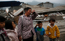 Chinese earthquake victims are seen in front of destroyed buildings in Lushan County of Ya'an,Sichuan Province, China, 22 April 2013. The Lushan Earthquake in Sichuan Province on 20 April 2013 resulted in 186 people dead, 21 missing, 11248 injured. About 1.72 million people were affected by the quake, while an initial estimate by the International Red Cross on Saturday put the number needing emergency shelter, water and food at 120,000. The China Earthquake Administration (CEA) recorded a magnitude 7.0 earthquake, while the US Geological Survey said it had measured 6.9.