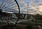 The sun sets on downtown Snoqualmie on a recent evening, on this antique wheel, old railroad tracks, and an old Methodist Church.