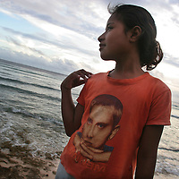 A young girl on the beach on the island of Kiribati wears a t-shirt bearing the image of American Rap musician Eminem. The islands of Kiribati in the South Pacific with their blue lagoon waters are endangered by rising sea water levels which are eroding the fragile atoll, home to approximately 92,000 people.