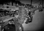 Tondo's slums are a hive of activity:  Man leaves one of Tondo's older slum's market with egg cartons.  Tondo, Manila, Philippines.<br /> <br /> Most of the vast slums of Manila's Tondo District in the Philippines are not only just a few meters above sea level but, in a seismically active area, are built on reclaimed land beside Manila Bay.  <br /> <br /> On Maplecroft's Climate Change Vulnerability Index, Manila ranks as the world's second most vulnerable city to climate change.  Manila's Tondo is Manila's district most vulnerable to climate change-induced sea rises, storm surges from increasingly strong typhoons and earthquake trigger tsunami.  It has a population density of nearly 78,000 people per square km (202,800 ppl/sq mi), according to a 2009 Cornell University report.  (Note: Manhattan has a population density of 26,939/km2 [69,771/sq mi].)