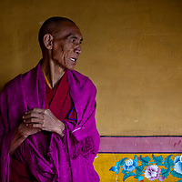 A Buddhist monk in Ladakh against a monastery wall.