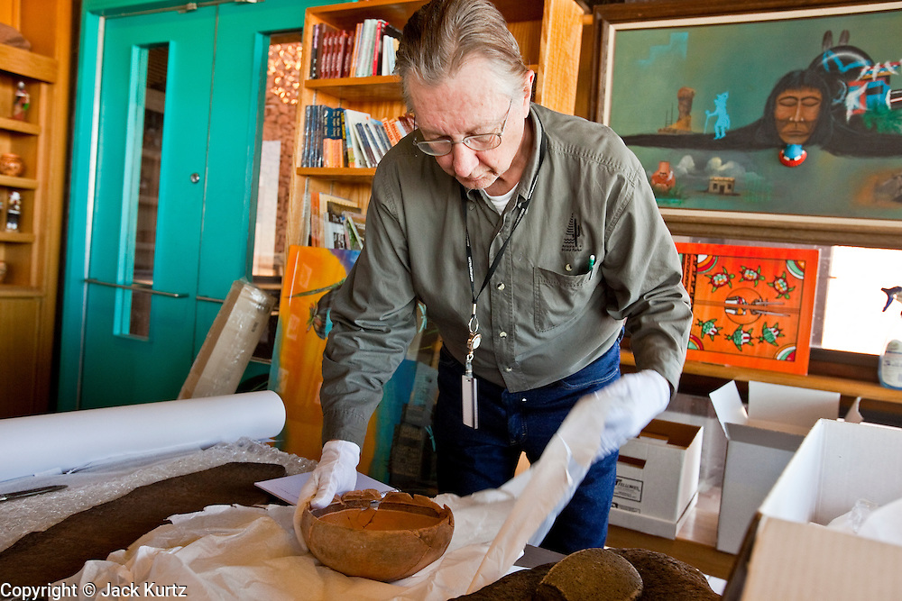 25 FEBRUARY 2010 -- WINSLOW, AZ: Curator Michael Freisinger (CQ) packs up artifacts, including a pre-Hispanic bowl, at Homolovi Ruins State Park north of Winslow. The park closed on Feb 22. The park's employees will spend the next few days packing up the park's exhibits but worry that the park's vulnerable archeological sites will be plundered by vandals and relic hunters when the park is vacant.   PHOTO BY JACK KURTZ