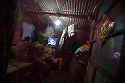 A picture made available on 30 July 2013 of Chinese children watching television in a room of a slum or shanty town area by the second ring road of Beijing, a few hundred metres away from the prosperous Central Business District (CBD), separated only by a busy highway in China, 29 July 2013. Beijing announced plans to spend 500 billion yuan (61.5 billion euros) to renovate shanty towns within the fourth ring road according to local media. The five-year plan is expected to affect more than 230,000 households. China's massive urbanization push has resulted in the creation of large pockets of shanty towns and slums in urban areas as millions of migrant workers shifting to the cities are often priced out of city-centre properties. Slum or shanty town dwellers often live in dirty and cramped conditions, where they have no running water in their homes and have to share toilet and shower facilities.