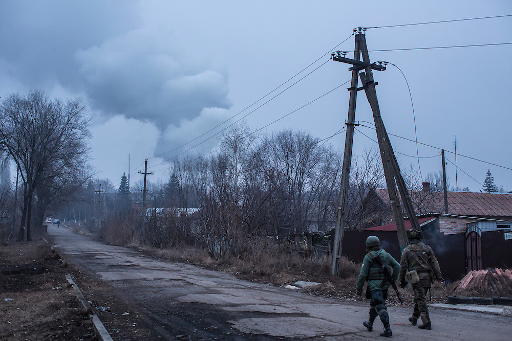 ARTEMIVSK, UKRAINE - FEBRUARY 14: Ukrainian fighters walk in the direction of a burning medical clinic that was hit by an artillery strike on February 14, 2015 in Artemivsk, Ukraine. A ceasefire between Ukrainian forces and pro-Russian rebels is scheduled to go into effect at midnight. (Photo by Brendan Hoffman/Getty Images) *** Local Caption ***
