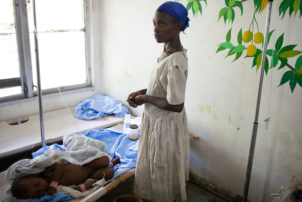 A mother watches over her daughter, who is sick with cholera, at the Hospital Albert Schweitzer on Saturday, October 30, 2010 in Deschapelles, Haiti.
