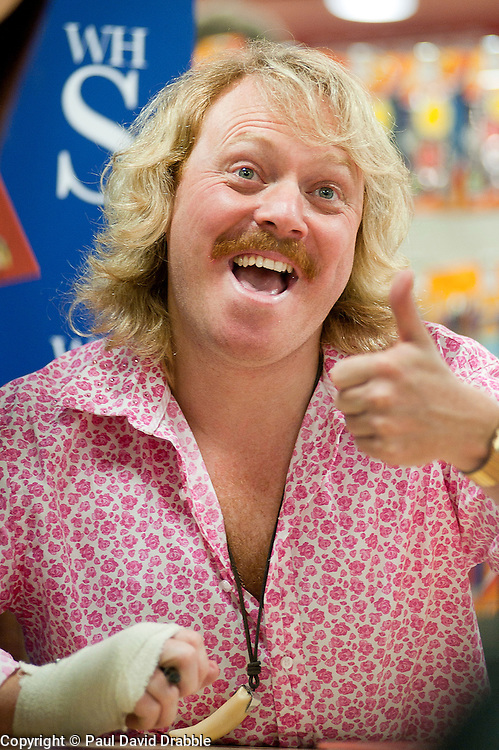 """Whith his right hand bandaged Leigh Francis in character as TV JUICE host Keith Lemon poses for photos with fans while signing copies of his new book. 'Keith Lemon: The Rules""""  when he stopped in at WHSmith Meadowhall shopping centre in Sheffield. The event scheduled for 5:00 - 5:30 was so popular that Keith started signing early and didn't finish until 7:05pm as well as sales of the book being restricted.  .1st November 2011. Image © Paul David Drabble"""