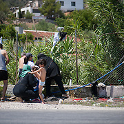 A refugee family washes by the main road outside the Kara Tepe camp. There are few water taps  in the camp