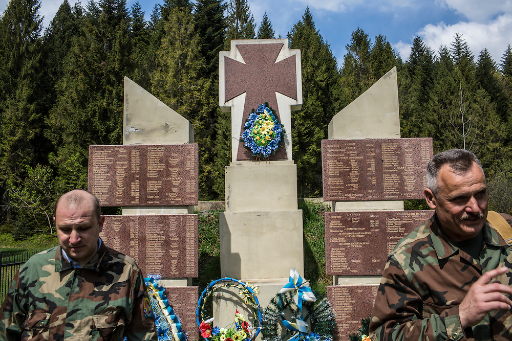 SKOLE, UKRAINE - MAY 1, 2015: Svyatoslav Sheremeta, left, and Volodymyr Kharchuk, director and deputy director of the organization Dolya, respectively, pay their respects at a memorial to local fighters killed in World War II in Skole, Ukraine. Dolya was formed to excavate and repatriate remains from World War II, though its focus is often on locating the graves of Ukrainian partisans killed by Soviet forces. CREDIT: Brendan Hoffman for The New York Times