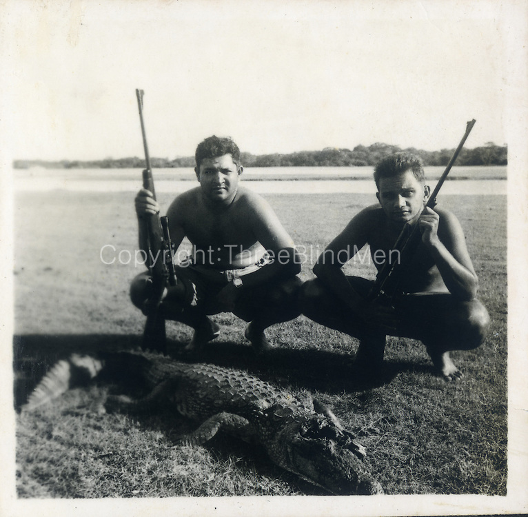 """""""The croc hunters are Dr Lance Fernando (with the telescopic sight on his rifle) & Shirley Andrado. Date is Nov 53 at Bagura & the croc was in the lagoon or actually basking on the bank. The rifle is a .270 Winchester."""""""