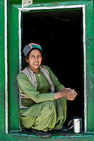 A Kinnauri Woman sits in the doorway of a small school room in Sunam Village in the Ropa Valley of Himachal Pradesh, India