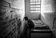 BARQUISIMETO, VENEZUELA - JULY 28, 2016: Iris Rodríguez, a patient who suffers from organic psychosis and mental retardation, and who was abandoned by her family,  rocks back in forth for hours at a time in her solitary confinement cell. She is not violent, but the nursing staff keeps her locked in isolation because she eats things that she shouldn't when she is left to roam around the women's ward and patio with other patients. The economic crisis that has left Venezuela with little hard currency has also severely affected its public health system, crippling hospitals like El Pampero Psychiatric Hospital by leaving it without the resources it needs to take care of patients living there, the majority of whom have been abandoned by their families and rely completely on the state to meet their basic needs. PHOTO: Meridith Kohut for The New York Times