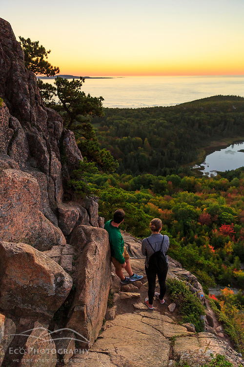 "A young couple awaits sunrise while hiking ""The Beehive"" in fall in Maine's Acadia National Park."