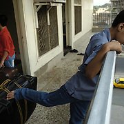 Farhad Dost age 15 looks over the railing of the family's apartment as the family's luggage is moved out the door the morning he and his family depart on their journey to Canada. Photo by Louie Palu/The Globe and Mail ©