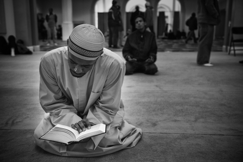 A man sits and quietly recites Quran after he finishes his prayer.