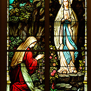A stained glass window at St. Francis Xavier Church in Superior depicts the Blessed Mother appearing to Bernadette Soubirous in Lourdes, France.