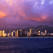 Luxury hotels lining famed Waikiki Beach glisten in the evening light as outrigger canoes glide along the shoreline.