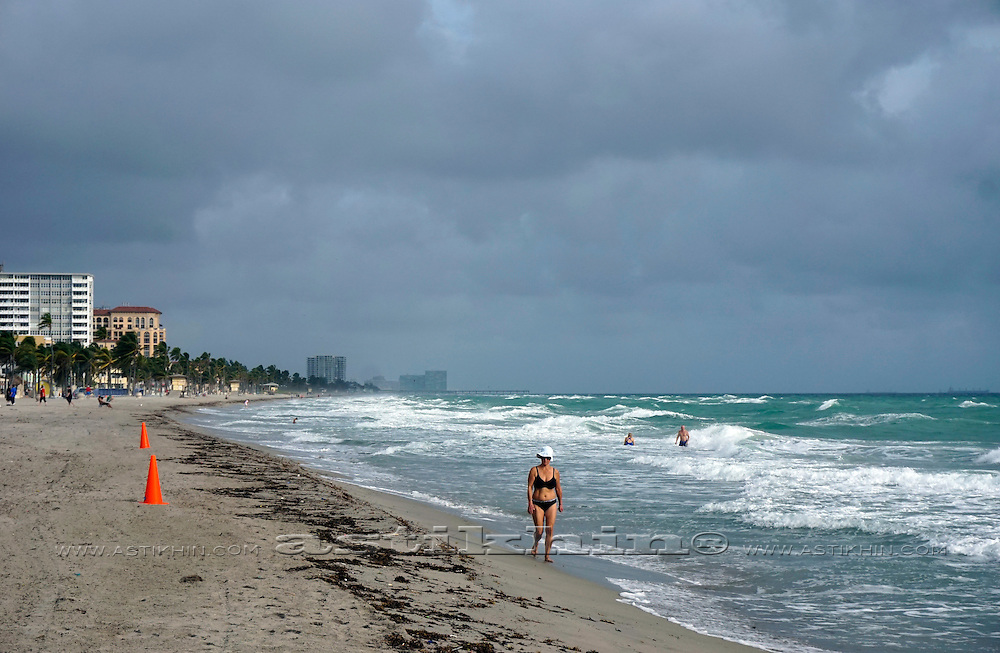 A Florida beach with tourists in the distance and waves breaking on the shore.