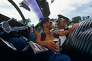 Seen from a low angle inside their open-top classic American car, two openly gay men cuddle up close to look into each other's eyes while holding their favourite cans of Websters Yorkshire bitter (beer). They are attending a classic car rally in Brighton during a Gay Pride festival, that this English seaside town regularly hosts during the hot south coast summers. The large 60s steering wheel is seen in the foreground and the vehicle's leather seat looks shiny clean against the bright light. There is a classic car magazine resting on one man's knee and they are clearly mad about this era of motor transportation.