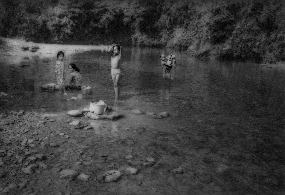 Iban Dayak girls in women's bathing area for Rumah Enggin longhouse, Sarawak, Malaysian Borneo.