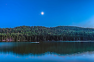 The quarter Moon reflected in the waters of Reesor Lake, Alberta in Cypress Hills Interprovincial Park. Taken on July 5, 2014. This is with the 10-22mm Canon lens and Canon 60Da at ISO400. This is a high dynamic range stack of 6 exposures from 0.6 to 13 seconds. The Moon was in conjunction with Mars (right of Moon) and Spica (left of Moon).