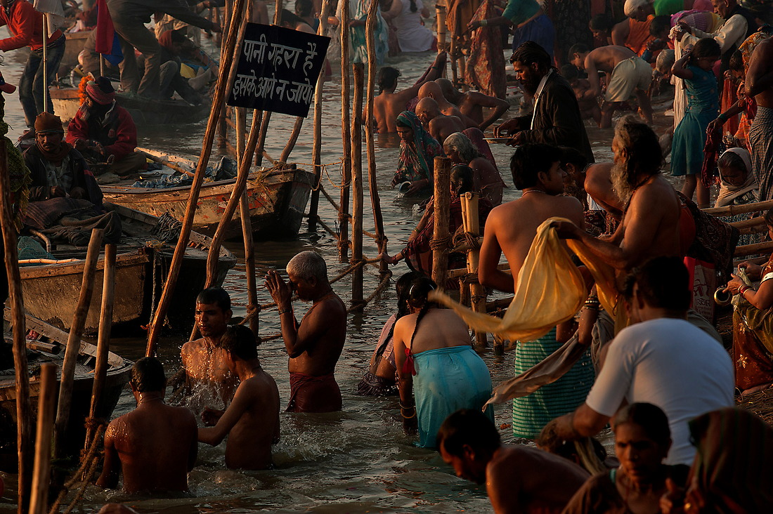 A lone Hindu man is deep in prayer amongst the crowd of other pilgrims during his ritual bath on February 9, 2013 in Allahabad, India during the Kumbh Mela. — © Jeremy Lock/