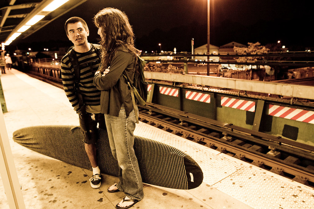 Two surfers wait with a surfboard for the L Train back into Manhattan en route from Rockaway Beach, Queens, NY.