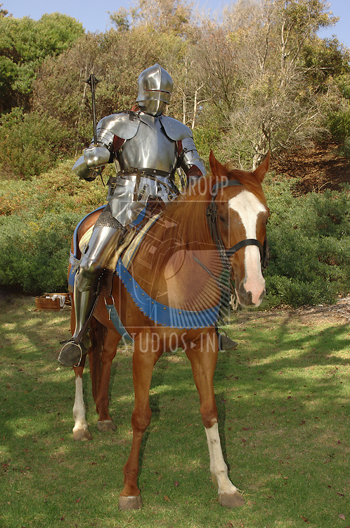 15th Century English knight in shining armour holding a mace while on horseback