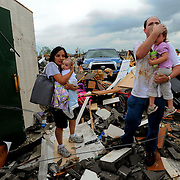 Photo by Gary Cosby Jr.    Homes in the McCulley Mill Rd. area are completely destroyed following a strike from an EF5 tornado that cut a path through Lawrence, Morgan and Limestone Counties.  Kevin Harrison and his wife Sarabeth hold their children, Mason and Sophie as they emerge from a safe room, the only part of their house to survive.