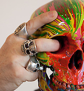 "Close-up Damien Hirst Portrait with fingers in eye sockets of skull of his artwork.""St Elmo's Fire"".2008.Household gloss on plastic skeleton.1700 x 425 x 435 mm.© Damien Hirst. All rights reserved, DACS 2010.Photographed in his Chalford Studio, near Stroud, Gloucestershire"